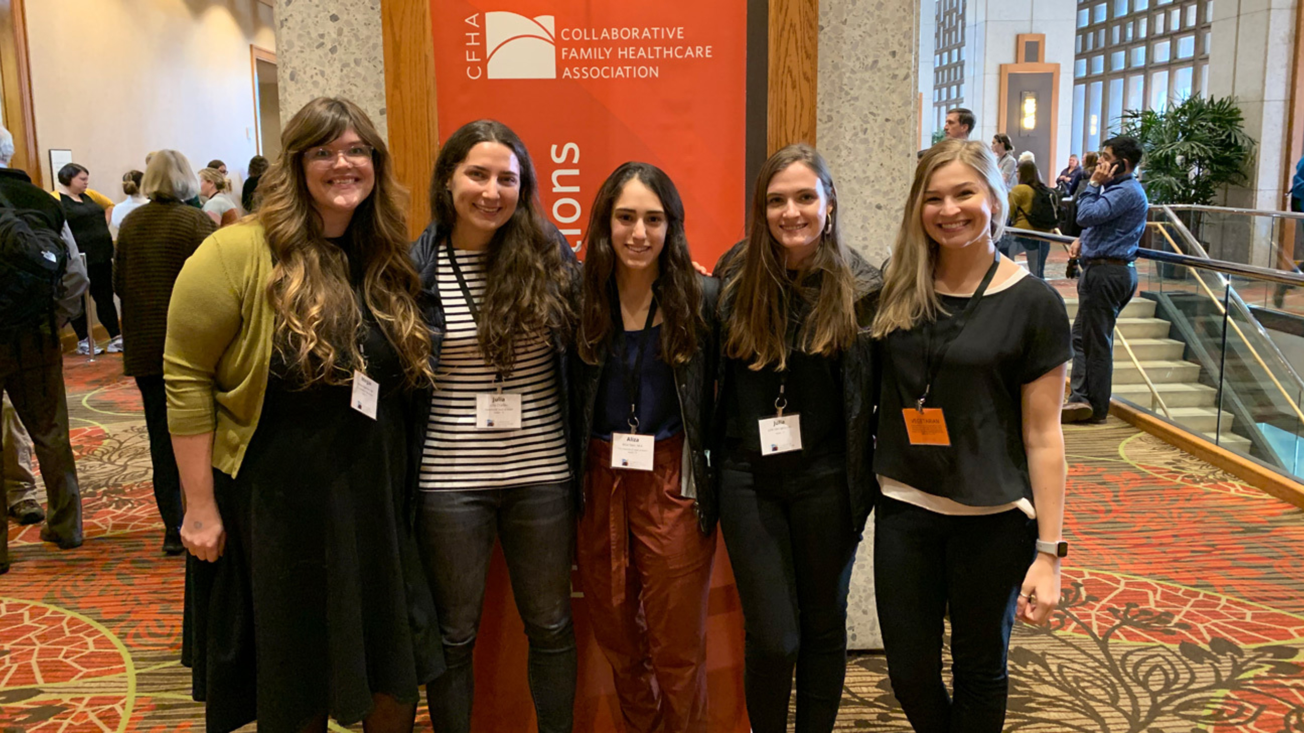 Five women who are part of the Integrated Behavioral Health Scholars program standing in a group together smiling at the camera at a conference.