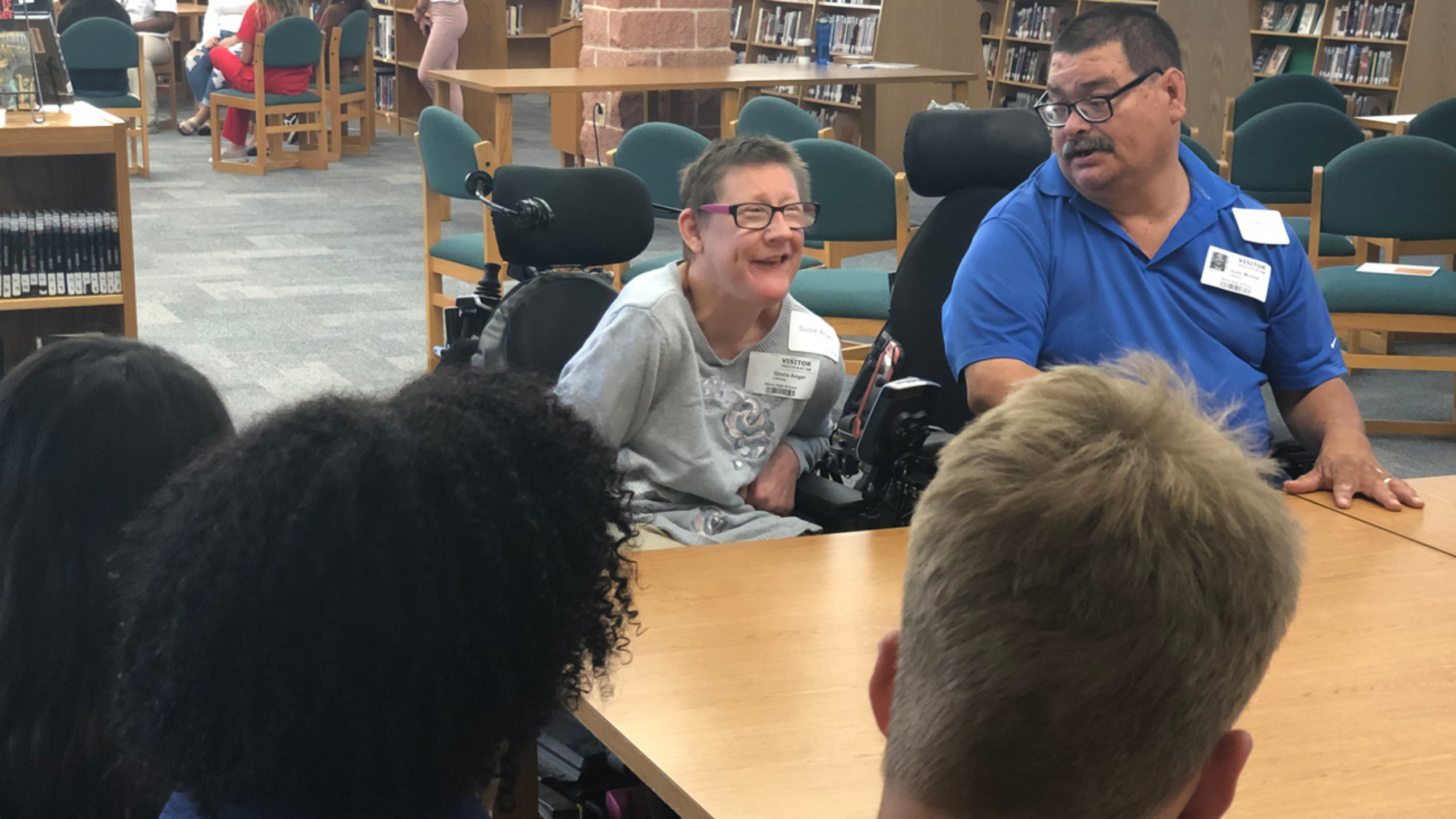 A man and a woman in wheelchairs speak to a group of students sitting at a table.