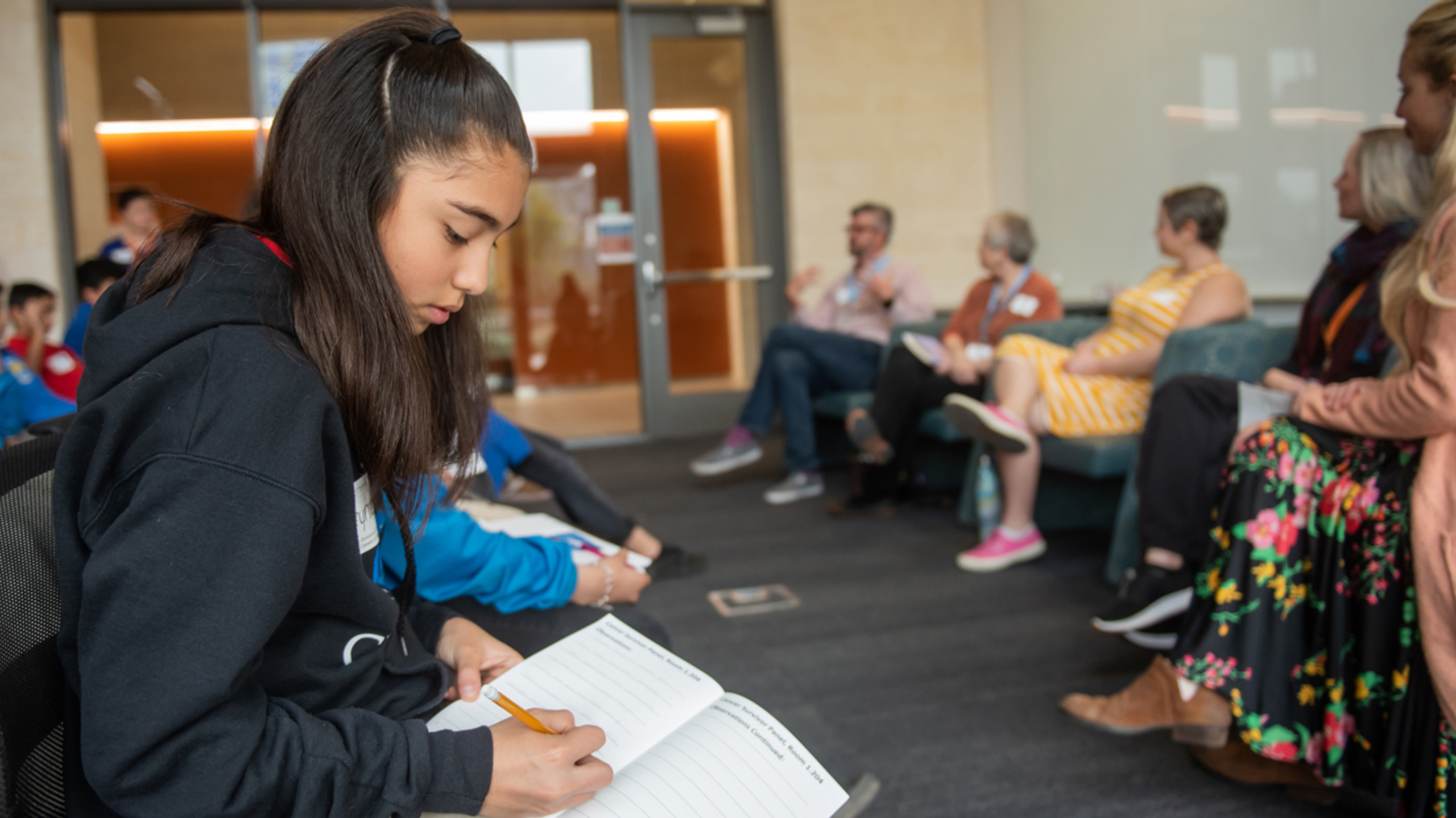 A middle school girl sitting in a chair taking notes during a panel discussion.
