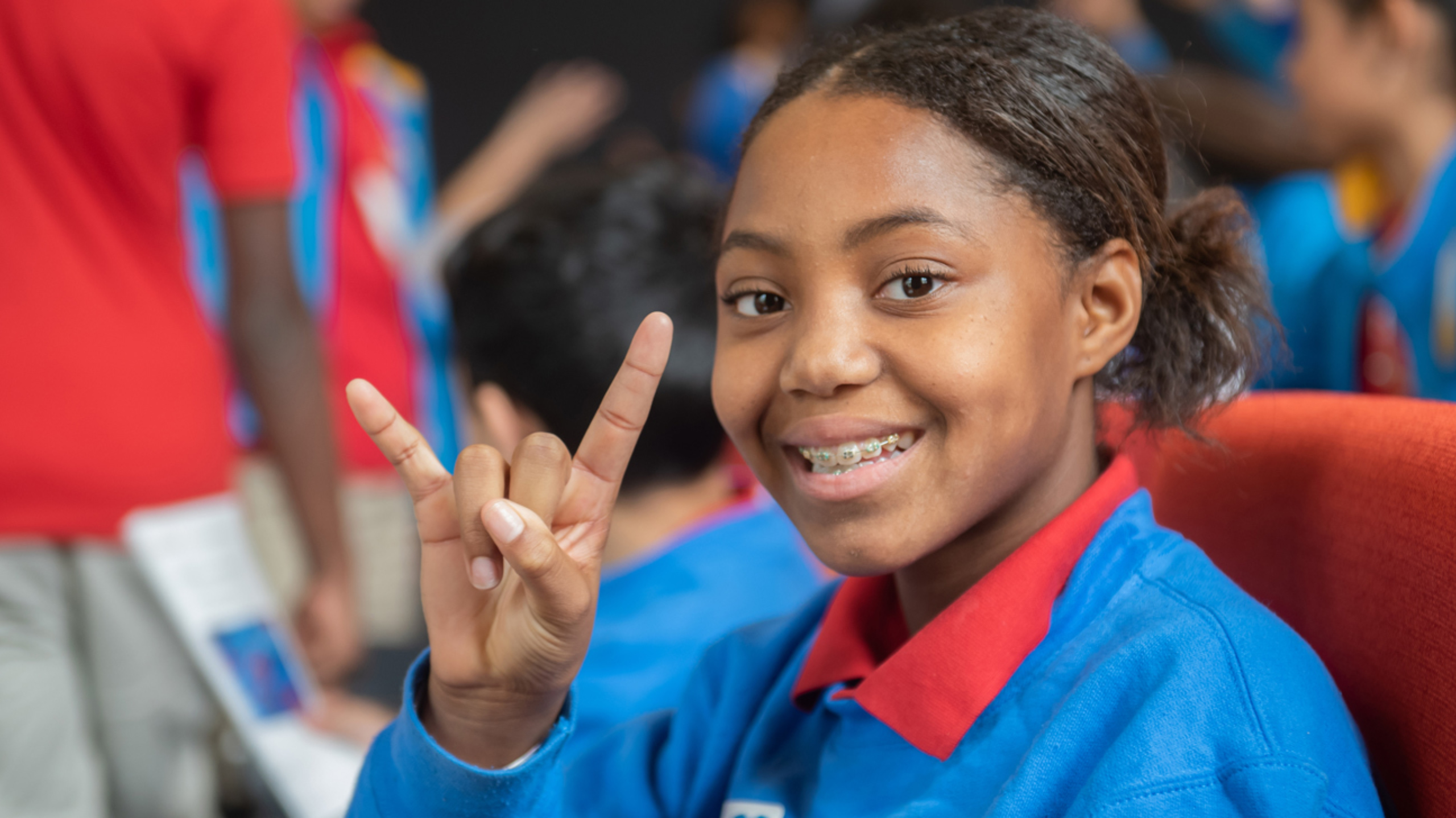 A middle school girl smiling and giving the hook 'em hand sign at the camera.