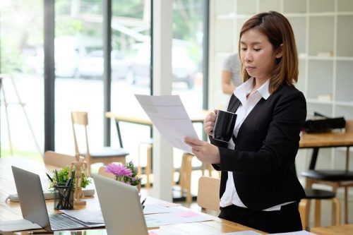 Female accountant looks at accounting certification requirements on paper