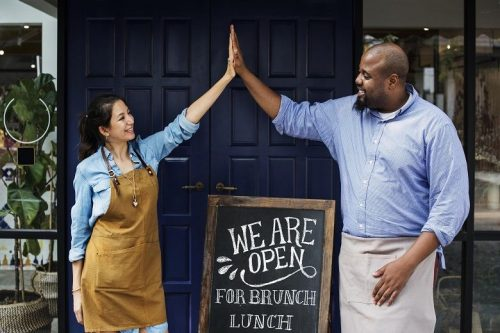 Two business owners cheerfully high five after opening restaurant