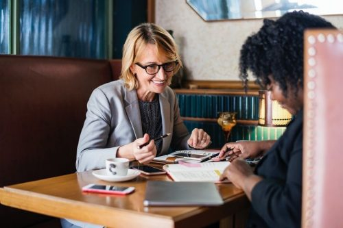 Two businesswomen, one older and one younger, sit at a booth in a restaurant and look at paperwork