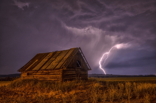 Lightning strike behind a barn.