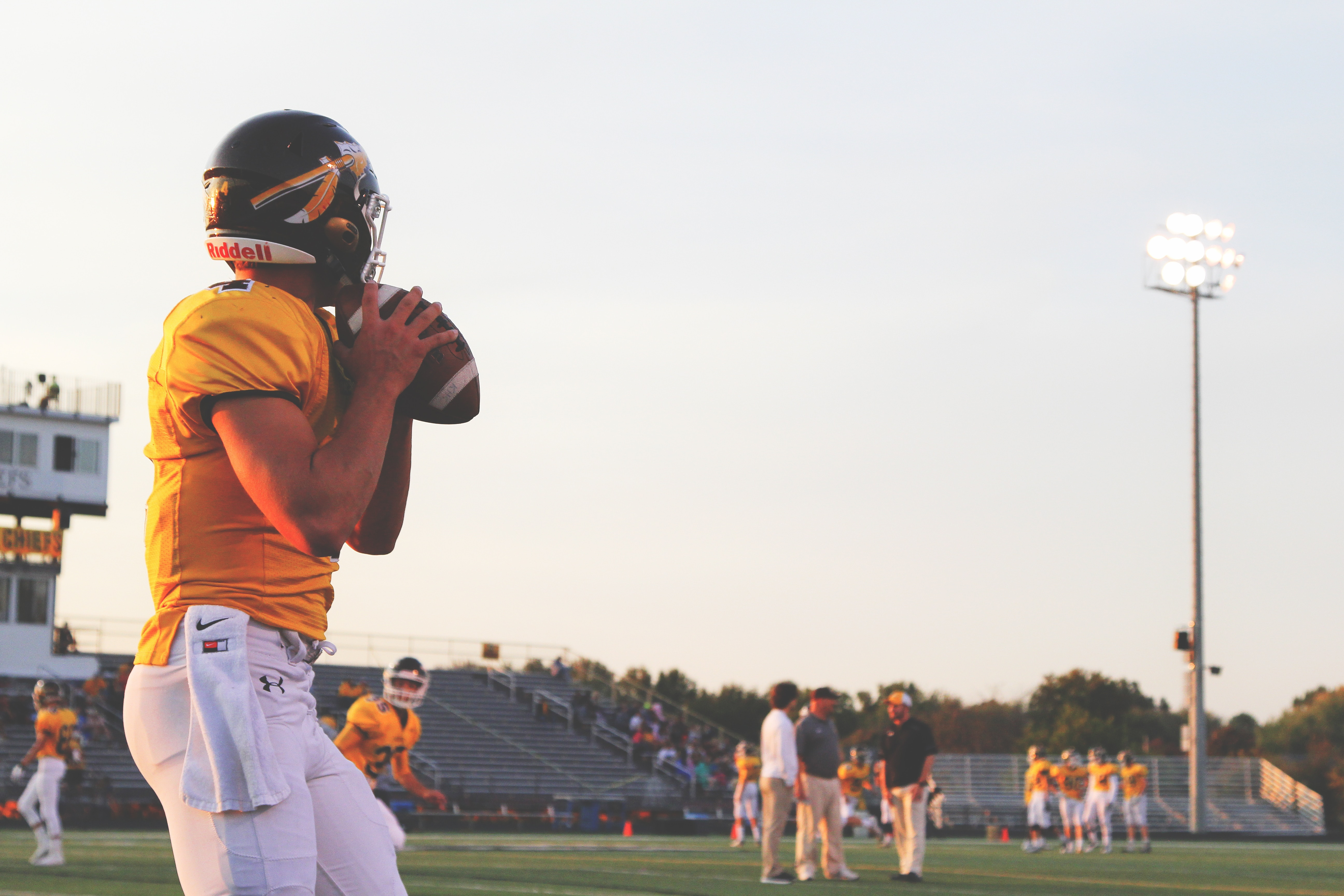 High school quarterback in yellow jersey getting ready to throw a football.