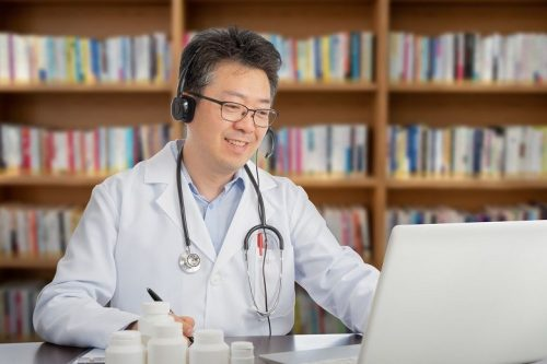A doctor in a white coat and wearing headphones uses a laptop to consult remotely with a patient.
