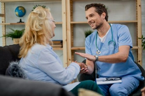 A smiling nurse in scrubs pats his patient's hand during a home visit.