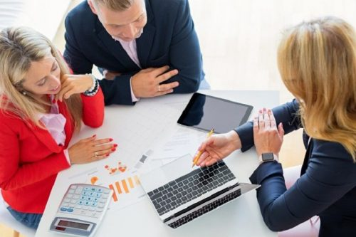 Several accountants sit at a desk reviewing data.