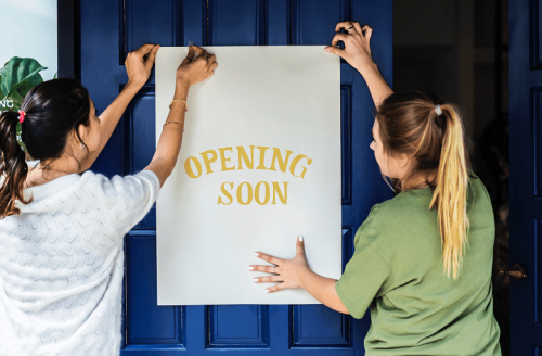 """Two business owners put up """"opening soon"""" sign onto the front door to their establishment."""