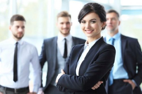A female working professional standing in front of a group of male working professionals