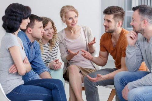 A group of people talk and smile while sitting in a semicircle.