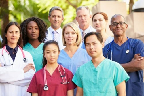 A medical team stands in front of a hospital.