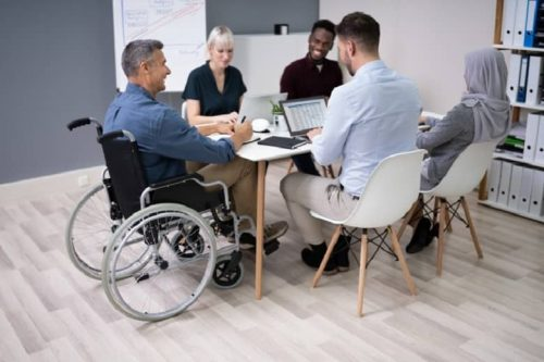 A mature businessman in a wheelchair meets with a diverse group of four co-workers in a small conference room.