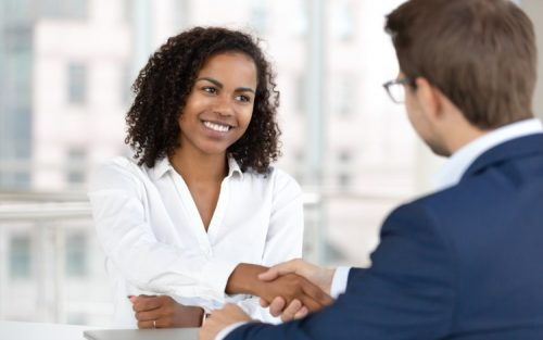 A smiling young employee relations manager welcomes a new hire to the company.