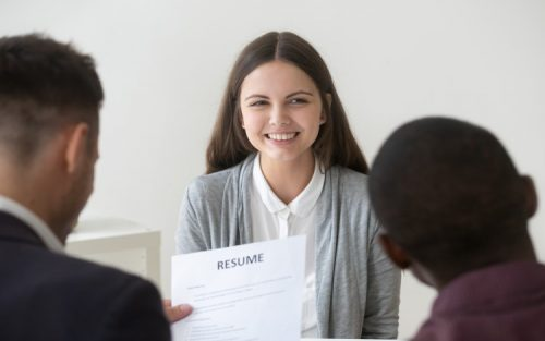 Two recruiting coordinators review the resume of a smiling female job candidate during a job interview.