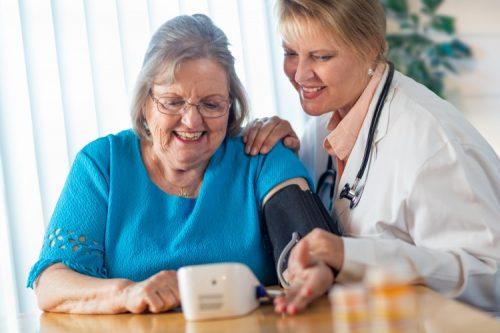 A home health nurse helps an older woman take her blood pressure.