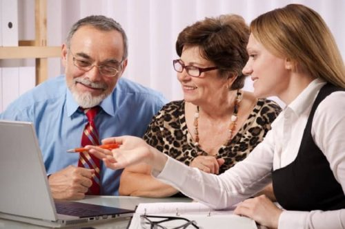 A personal financial adviser points at a laptop screen in a meeting with smiling clients.