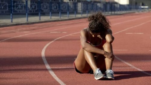 An anxious sprinter sits on the track, holding her head.