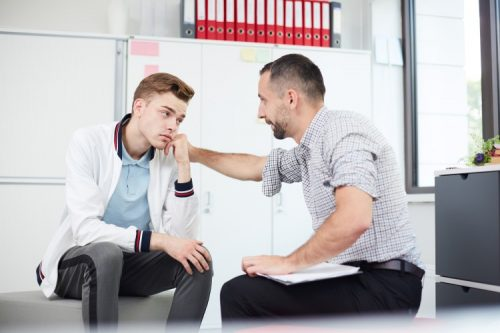 A mental health counselor comforts a teenager during a therapy session.