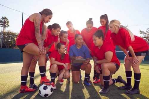A soccer coach huddles with her team.