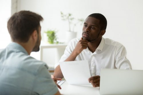 An HR manager interviewing a job candidate in his office.