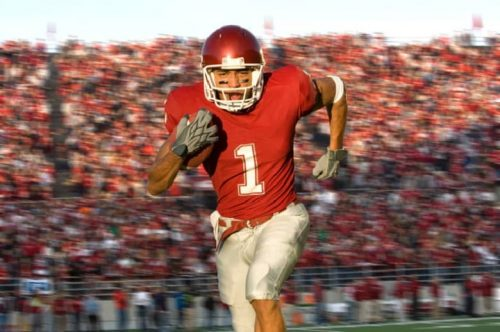 A football player running with the football down the field.