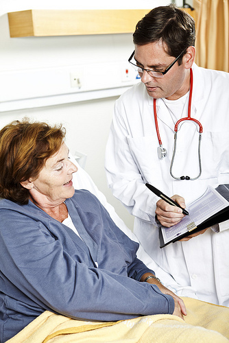Healthcare professional meets and consults with elderly female patient in hospital setting
