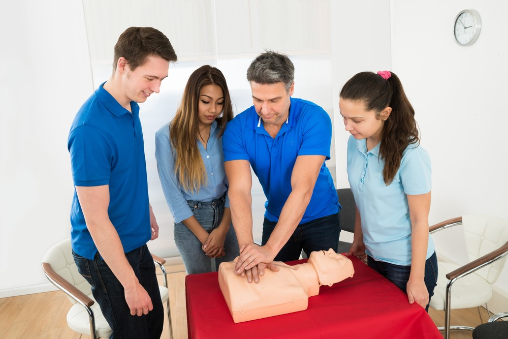 Instructor teaches three students CPR on a dummy.