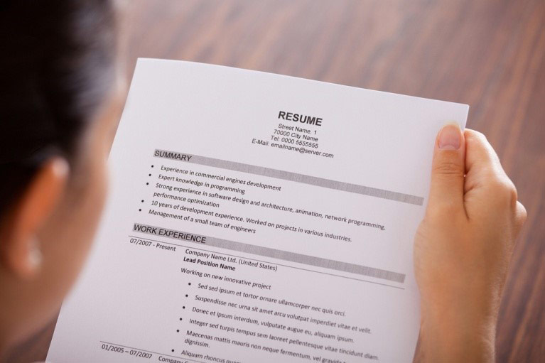 A woman looks over her nursing resume.