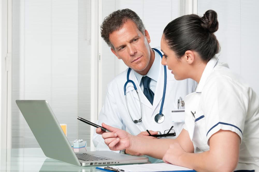 A doctor and a nurse discuss information on a laptop