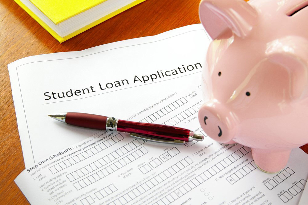 A student loan application sits on a table with a pink piggy bank and a red pen.