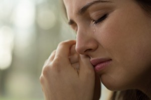 Woman crying clutching clasped hands to cheek.