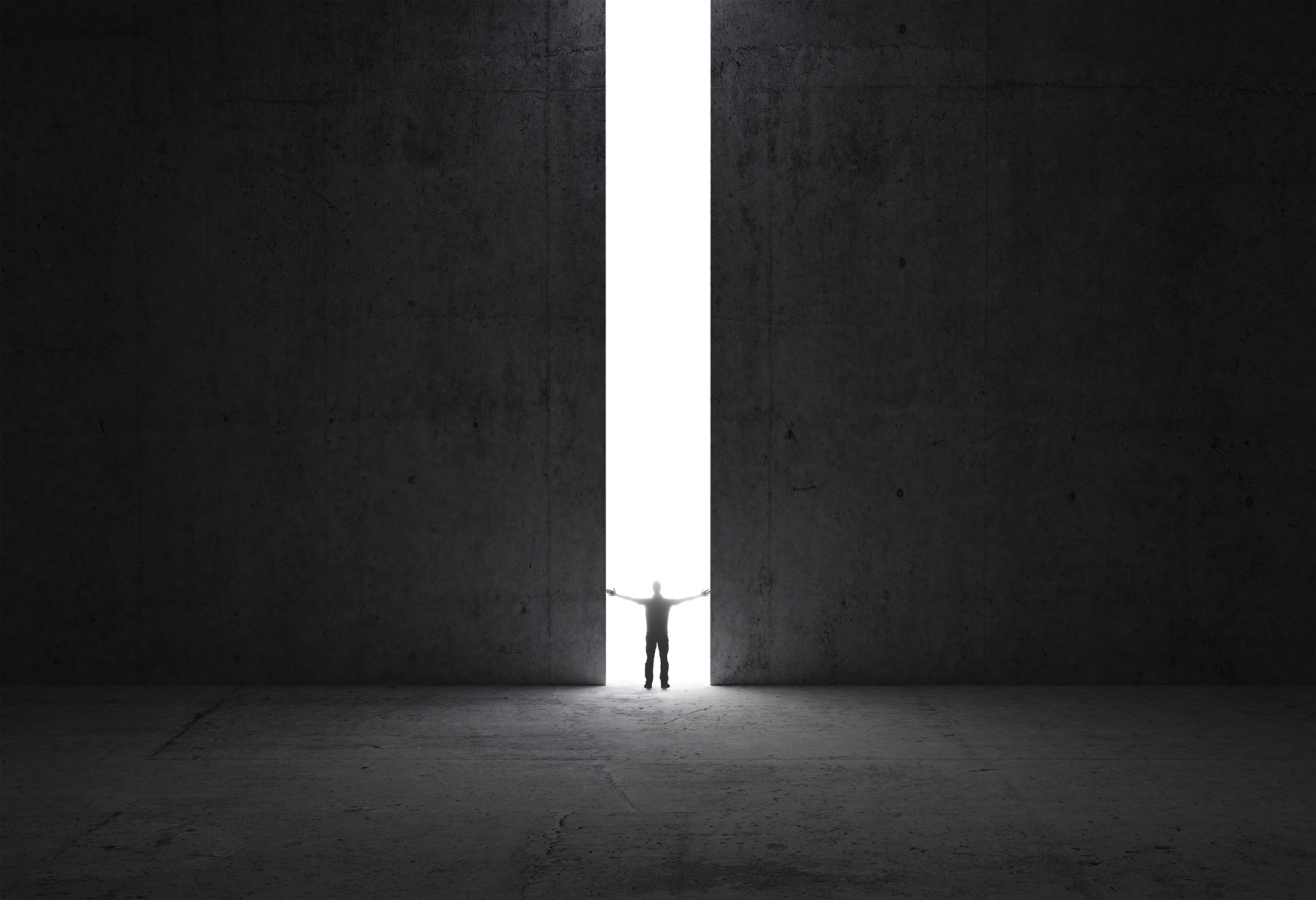 Silhouette of a person in the distance through a large crack of light in a wall