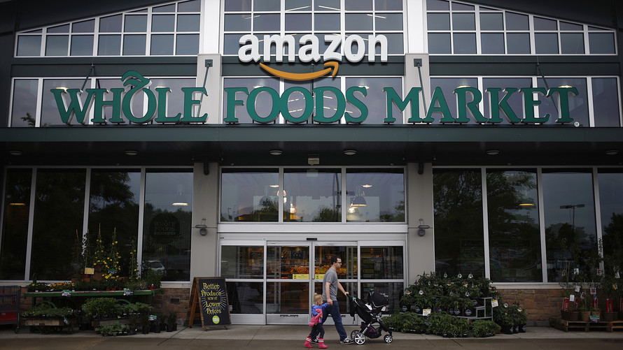 A family walks by Amazon Whole Foods Market store.
