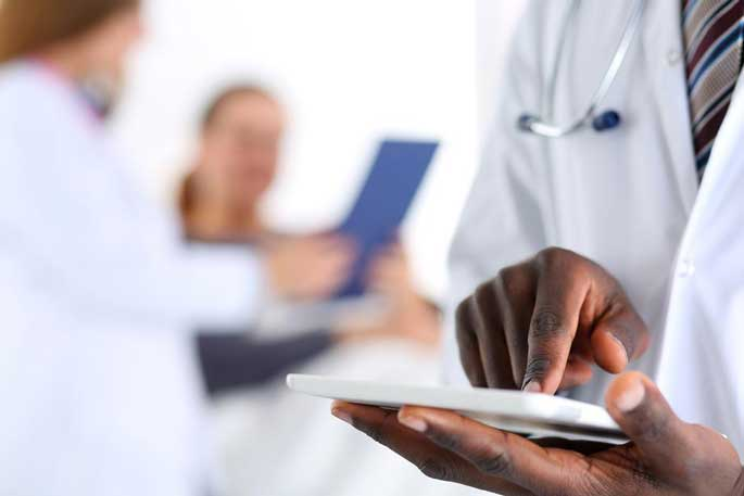 Three health professionals enter information on tablets