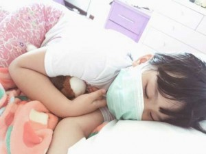 Young girl wearing flu mask while sleeping in bed