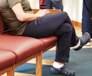 Patient in medical office waiting room uses smartphone