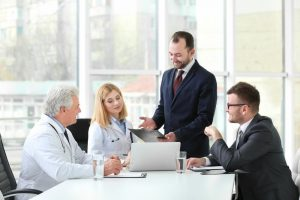 Medical professionals and business professionals work around a table.