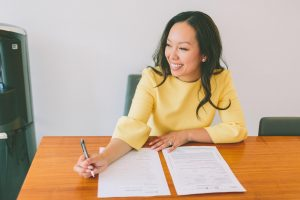 A woman working on documents and smiling at a table.