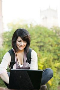 An MBA student works on an online assignment abroad.