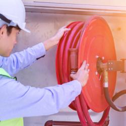 An fire safety technician analyzes a fire hose.