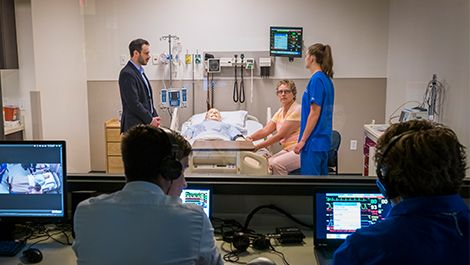 Two people observing a nurse speaking to a patient in bed and family members in a patient's room
