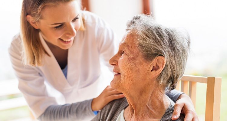 Smiling nurse with smiling older patient