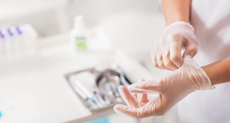 Nurse putting on gloves