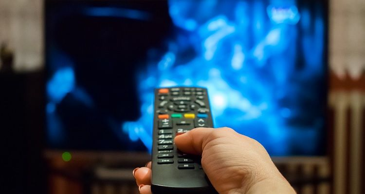 Woman hand with remote towards television