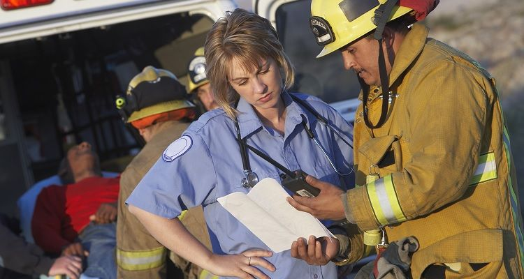 Firefighter reviewing information with nurse at a scene