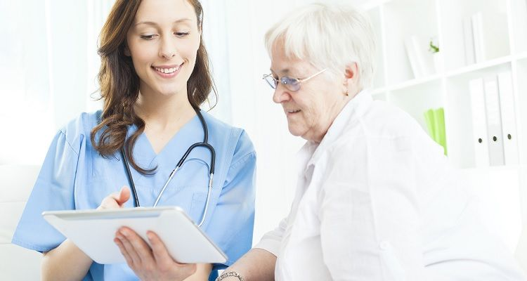 Nurses reviewing information on tablet with elderly patient