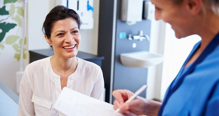 Smiling nurse interacting with patient