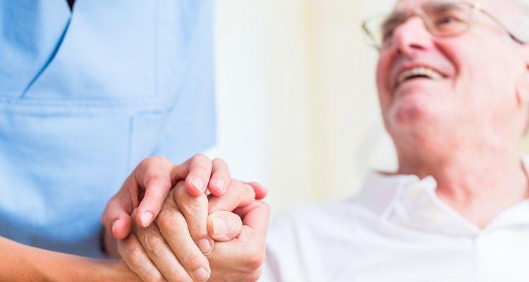 Nurse holding elderly patient mans hand