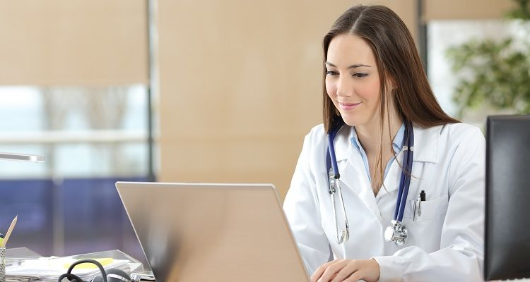 Smiling nurse using laptop